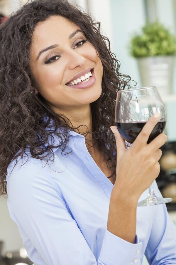 Vino rosso bevente sorridente della donna ispana fotografia stock