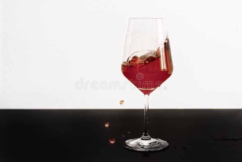 Vino rosso che spruzza da un vetro immagine stock libera da diritti