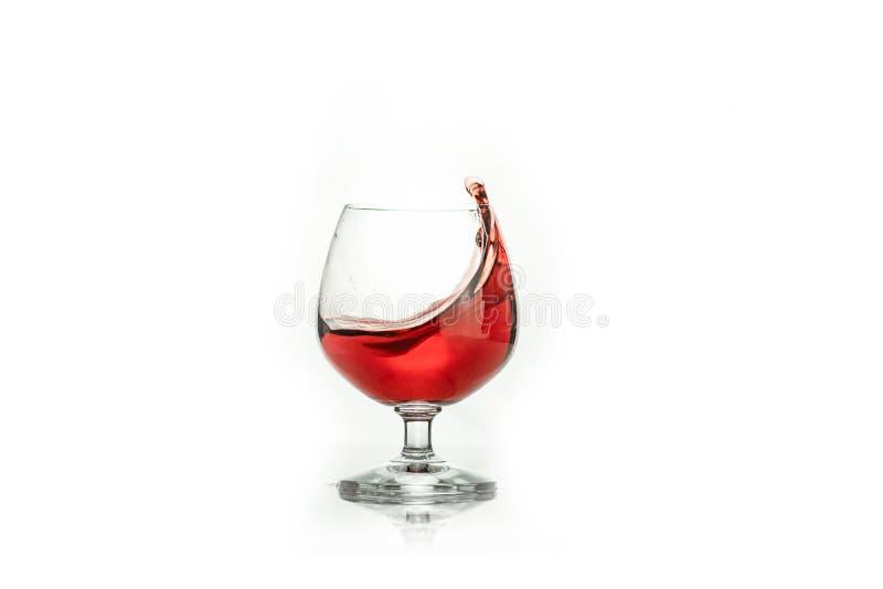 vino rosso che spruzza da un vetro, su bianco immagini stock