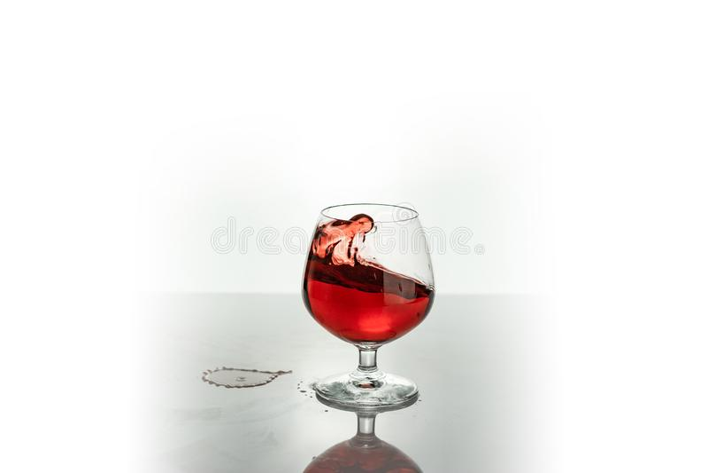 vino rosso che spruzza da un vetro, su bianco fotografia stock