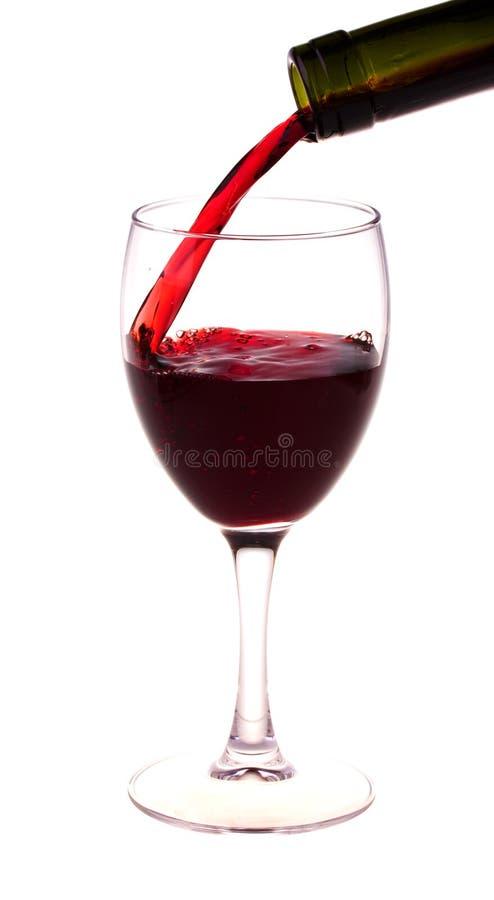 Vino rosso che versa da una bottiglia di vino fotografia stock