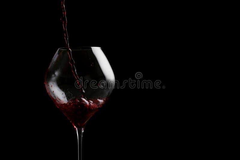 Vino rosso che versa in vino isolato sul nero immagine stock libera da diritti