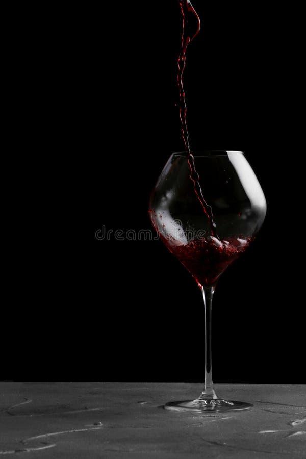 Vino rosso che versa in vino isolato sul nero fotografia stock