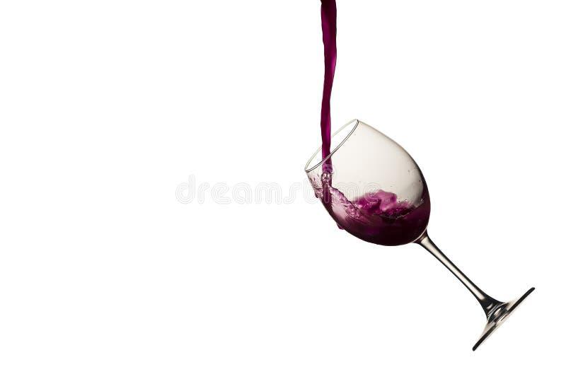 Vino rosso che versa in un bicchiere di vino su bianco isolato immagini stock libere da diritti
