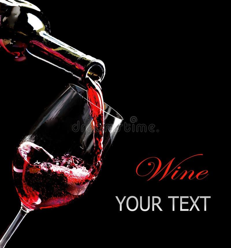 Vino rosso che versa in un vetro di vino immagini stock