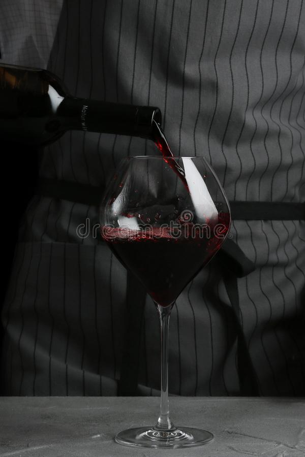 Vino rosso che versa in vetro barista sul concetto del cameriere su fondo nero immagini stock libere da diritti