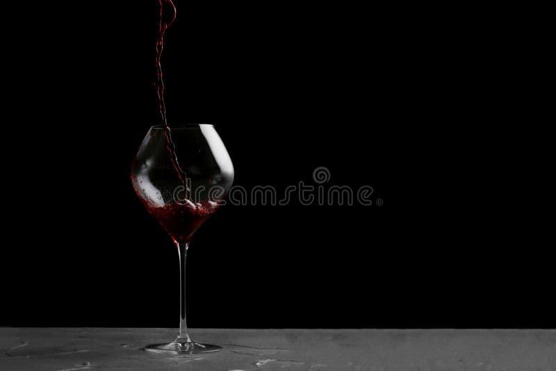 Vino rosso che versa in vetro isolato sul nero immagini stock