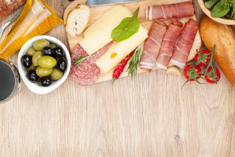 Vino rosso con formaggio, olive, i pomodori, il prosciutto di Parma, il pane e lo PS immagine stock libera da diritti