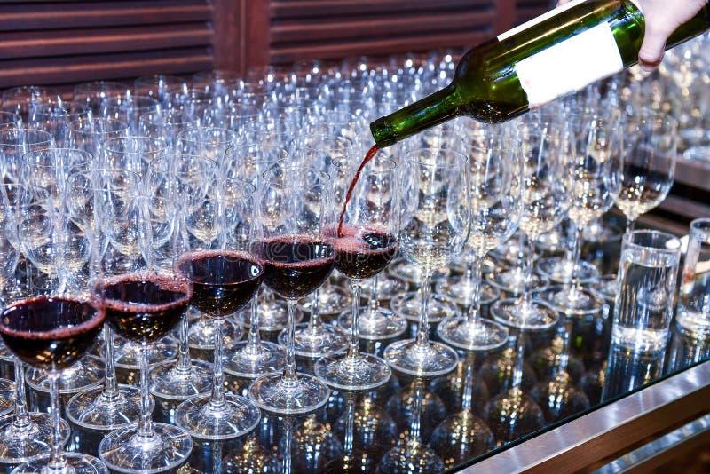 Vino rosso di versamento ai vetri per servire immagini stock libere da diritti