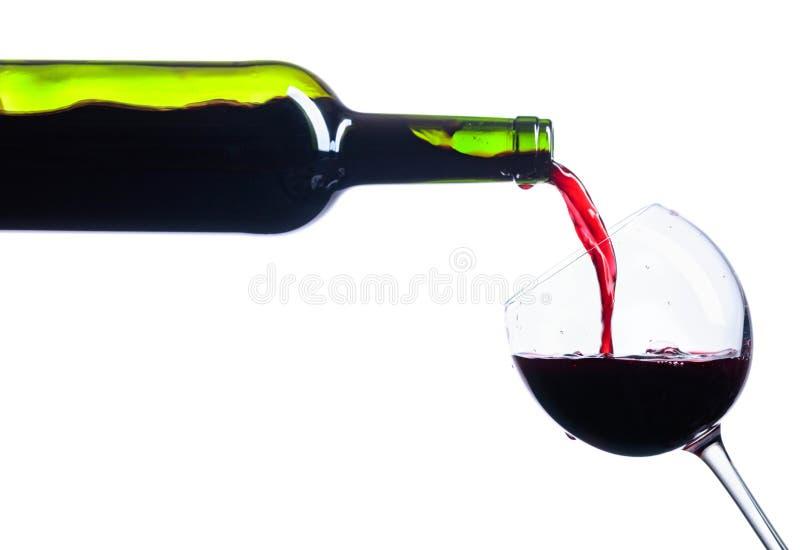 Vino rosso di versamento dalla bottiglia a vetro isolato su bianco immagini stock