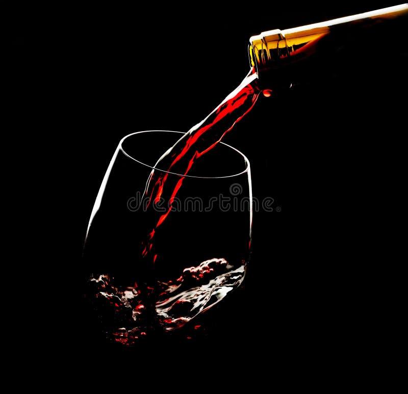 Vino rosso di versamento nel vetro contro fondo nero immagini stock