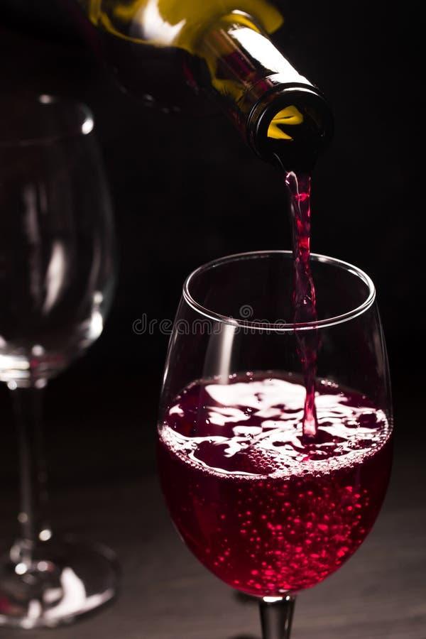 Vino rosso di versamento su buio immagini stock libere da diritti