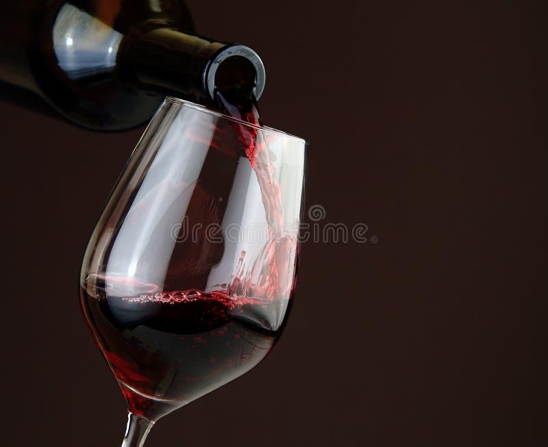 Vino rosso di versamento su fondo scuro fotografia stock