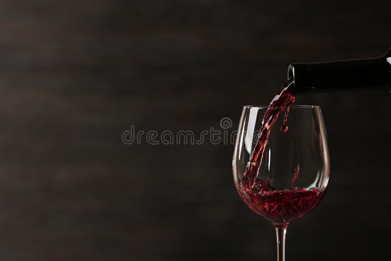 Vino rosso di versamento in vetro dalla bottiglia contro fondo scuro Spazio per testo fotografie stock
