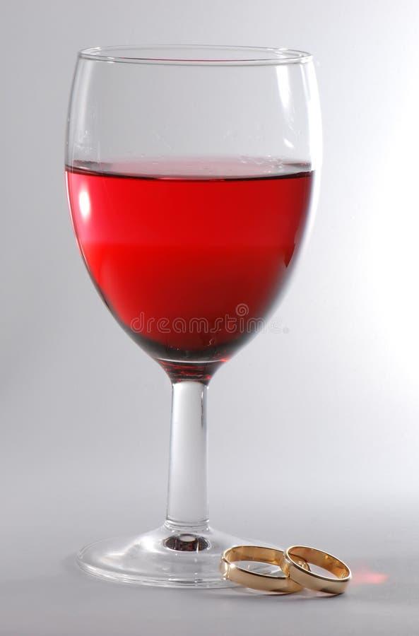 Vino rosso ed anelli di cerimonia nuziale immagine stock