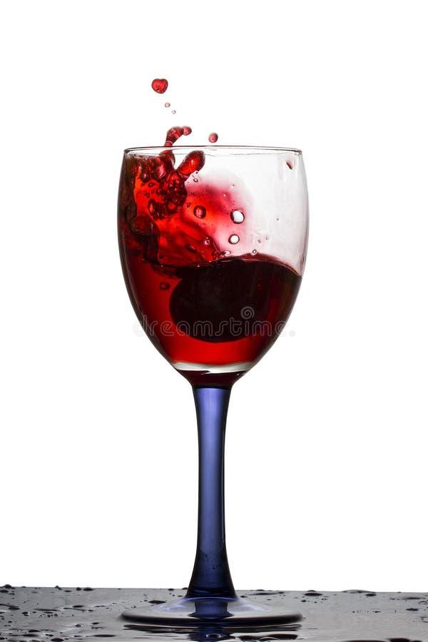 Vino rosso luminoso che spruzza in un vetro con l'uva caduta fotografie stock