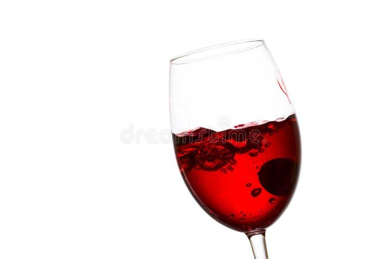 Vino rosso luminoso in un vetro inclinato dentro il quale una spruzzata fotografia stock libera da diritti