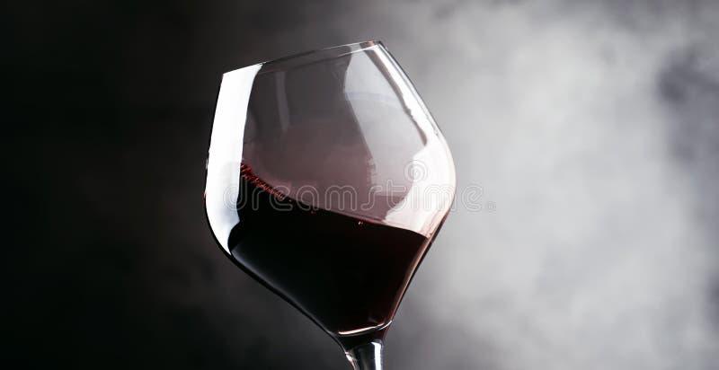 Vino rosso, spruzzata in un Cabernet-Sauvignon di vetro e asciutto, backgr scuro fotografia stock