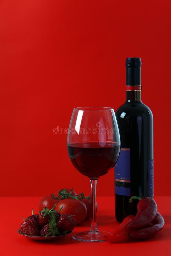 Vino rosso su priorità bassa rossa con colore rosso fotografie stock