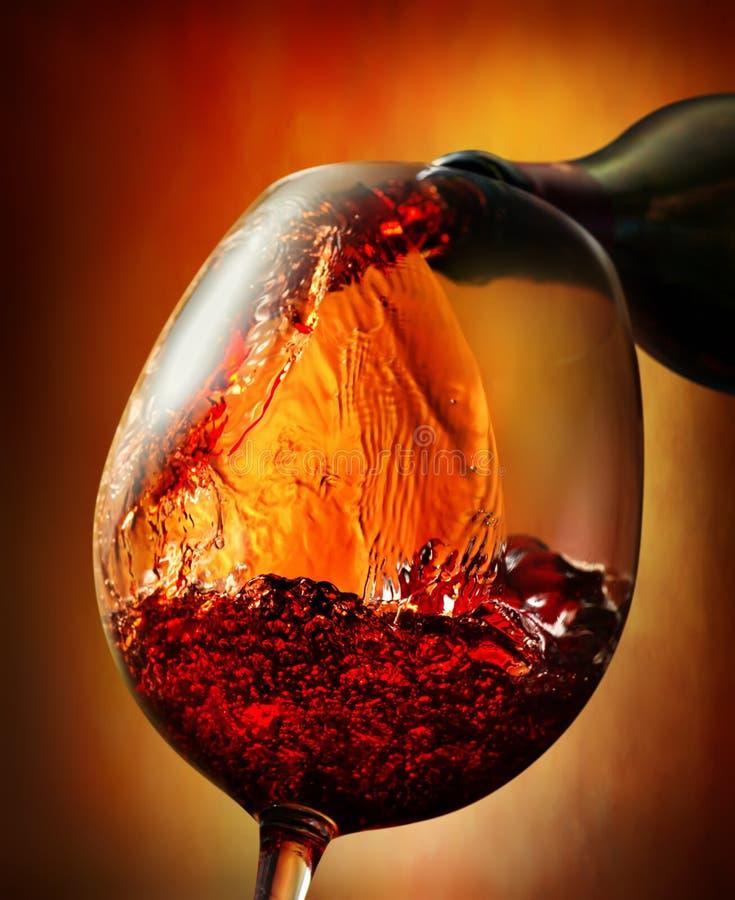 Vino rosso su un fondo arancio immagine stock