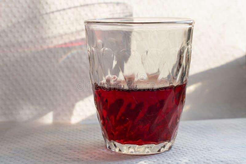vino rosso in una tazza di vetro su una tavola bianca con una bella ombra immagine stock