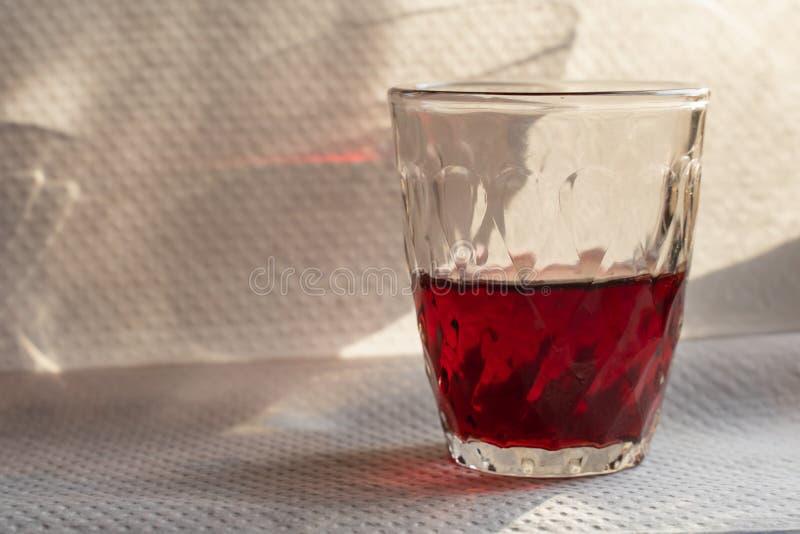 vino rosso in una tazza di vetro su una tavola bianca con una bella ombra fotografia stock