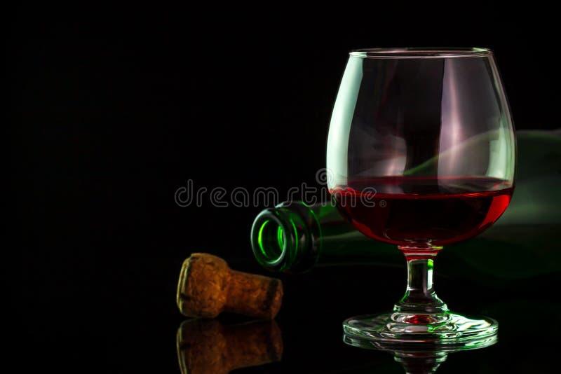Vino rosso in vetro e bottiglie sulla tavola fotografie stock libere da diritti