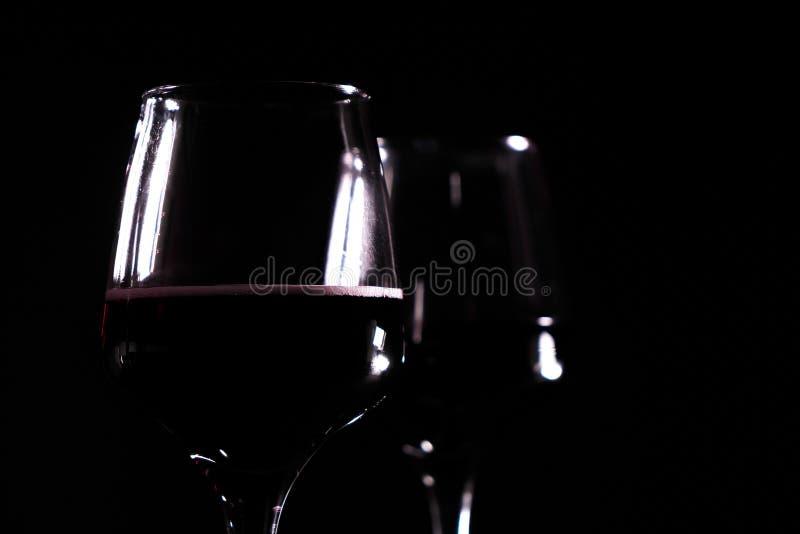 vino rosso in vetro sui precedenti neri fotografia stock libera da diritti