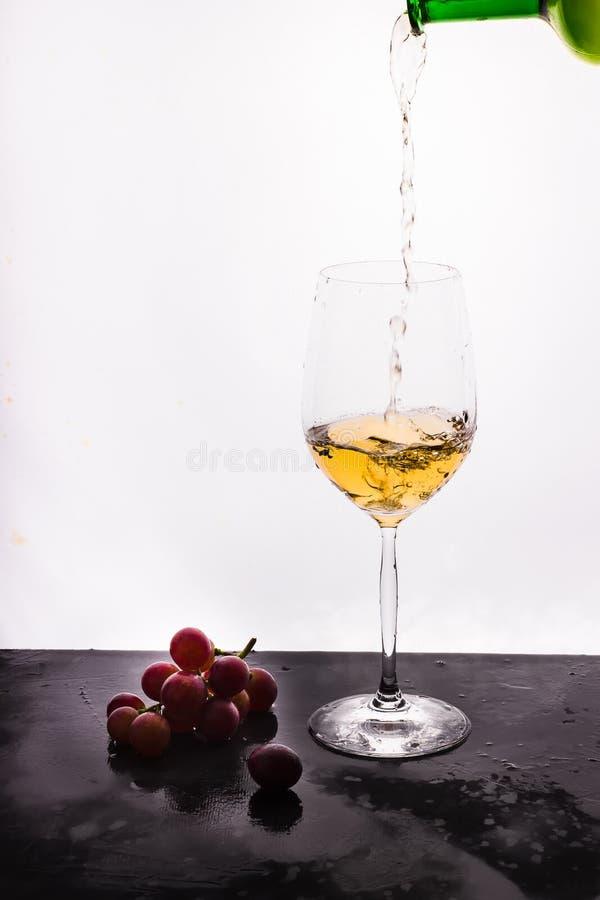 Vino scorrente su fondo e sull'uva bianchi fotografia stock
