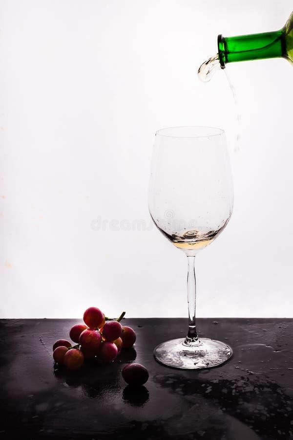 Vino scorrente su fondo e sull'uva bianchi immagini stock libere da diritti