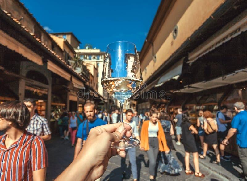 Vino secco in vetro sopra la folla turistica al ponte di pietra di Firenze, Toscana Città antica in Italia Sito di eredità dell'U fotografie stock libere da diritti