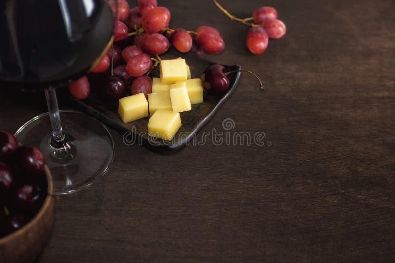 Vino, sheese, uva e ciliegia su fondo rustico scuro immagine stock