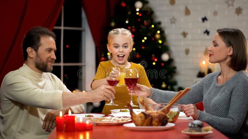 Vino tintinnante la vigilia di natale, succo bevente del bambino, famiglia felice dei genitori che celebra fotografia stock