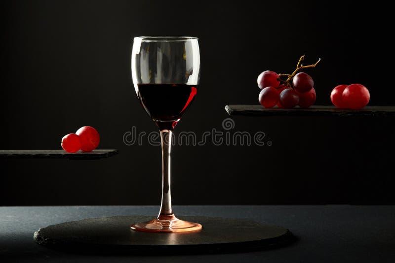 Vino tinto dulce en las bayas de cristal y frescas de la uva en fondo negro fotografía de archivo libre de regalías
