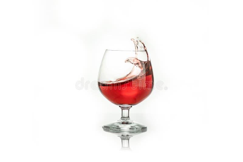 vino tinto que salpica fuera de un vidrio, en blanco fotografía de archivo