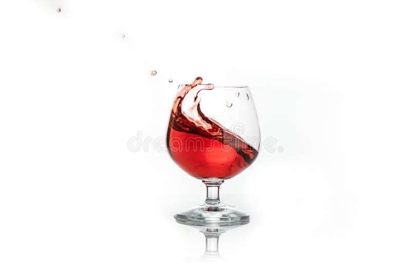 vino tinto que salpica fuera de un vidrio, en blanco fotos de archivo
