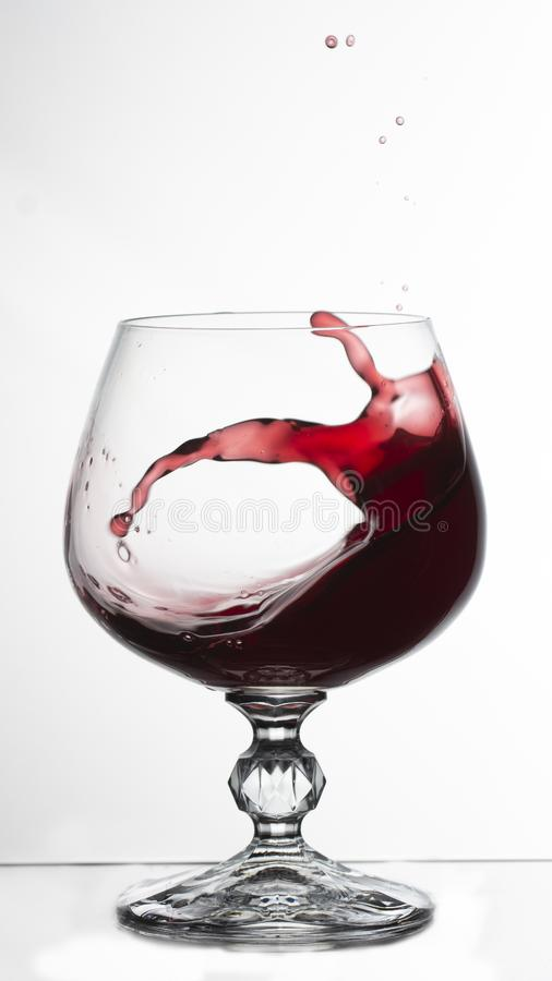 vino tinto que salpica fuera de un vidrio, en el bacground blanco foto de archivo libre de regalías