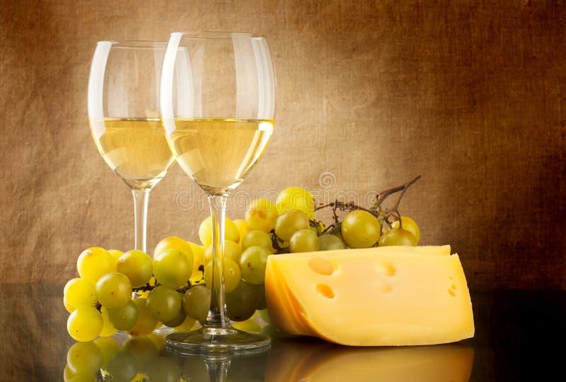 Vino, un manojo de uvas blancas y un pedazo de queso fotos de archivo