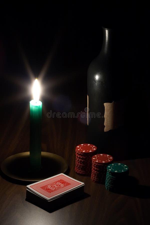 Vino, vela, tarjetas que juegan y virutas fotografía de archivo