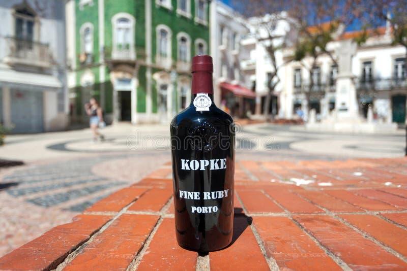 Vino vermiglio fine di Oporto della cantina popolare di Kopke, bottiglia del bevitore sulla via soleggiata della città immagine stock
