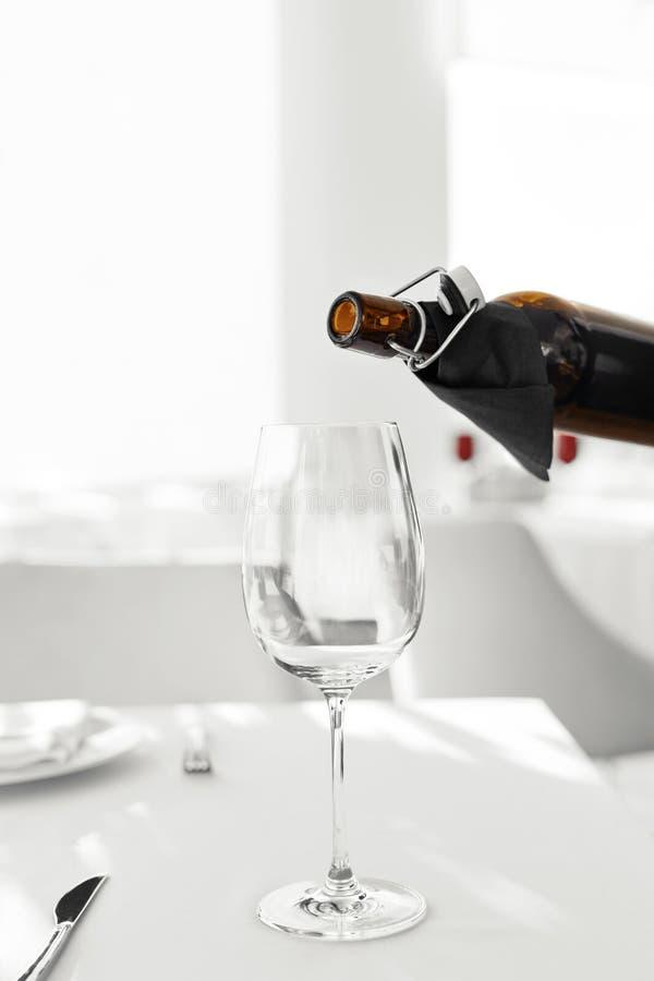 Vino Vino rosso di versamento dalla bottiglia nel vetro di vino bevande fotografia stock