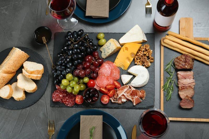 Vino y bocados servidos para la cena en la tabla en restaurante fotografía de archivo libre de regalías