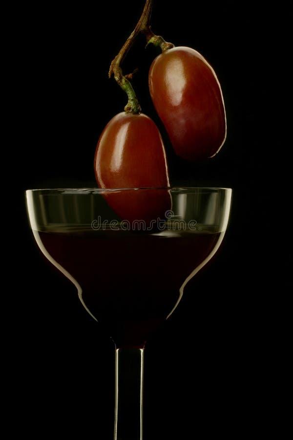 Vino y uva en fondo negro imagen de archivo