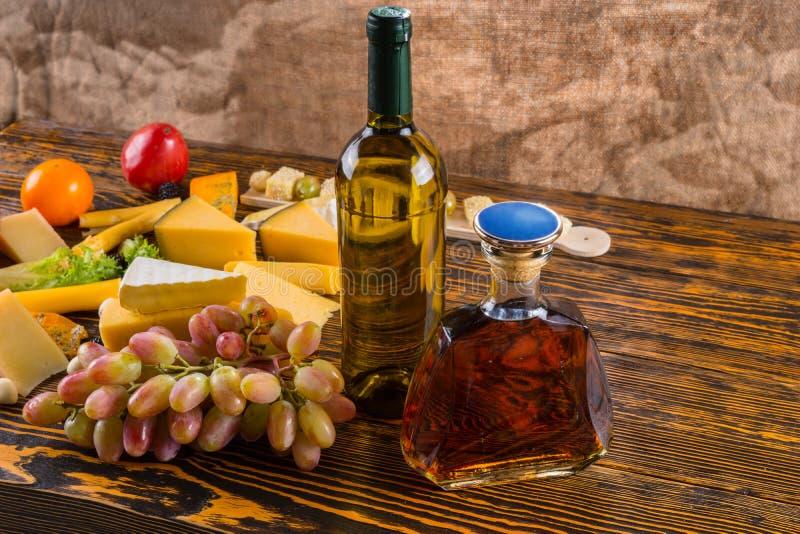 Vino y whisky en la tabla con queso y uvas imagen de archivo