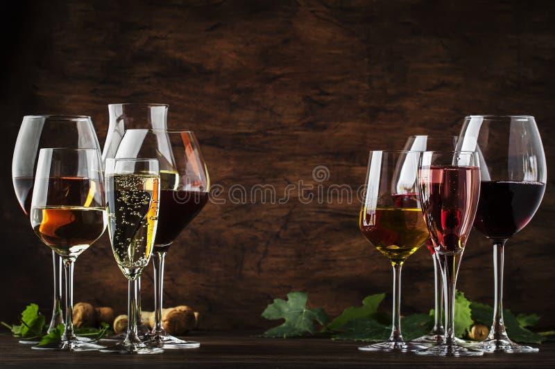 Vinos degustación, degustación y espuma. Vino rojo, blanco, rosa y champán ш т surtido en copas de vino en madera vintage imagenes de archivo