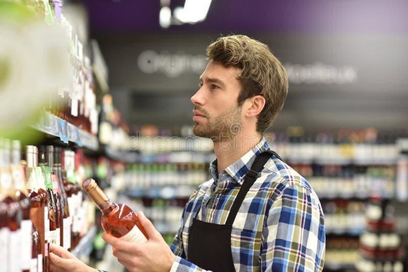 Vinpecialist i rader av supermarket royaltyfri fotografi