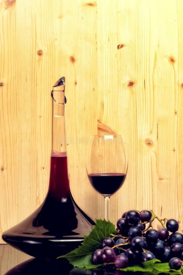 Vinsamlings-enexponeringsglas, flaska och druvor royaltyfri bild