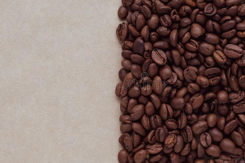 Vintage abstract pattern with black coffee beans on brown paper background. Copy space for text. Natural backdrop, cardboard textu royalty free stock image