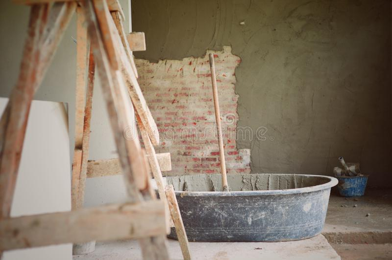 Vintage abstract picture of tools and cement cart mixer with the plastering wall at the construction site stock images