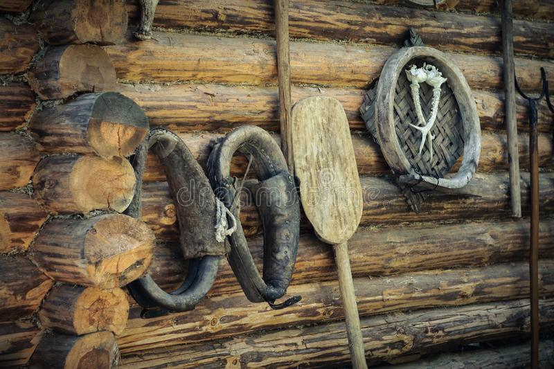 vintage accessories, old horse harness and household items on the background of a rough wooden log wall stock photography